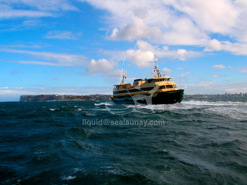 Manly Sydney Ferry passing Sydney Head in bad weather.