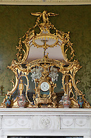A flamboyantly carved and gilded mirror hangs above the drawing room fireplace, in front of which are displayed a gilt clock and four Oriental vases