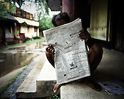 A villager is seen reading the newspaper outside his house in Dinghia village in Orissa, India.