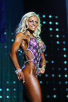Zivile Raudoniene Wins Figure International 2009. Zivile Raudoniene of Hickville, New York, w3alks onto the stage at the Figure International Championships at the Arnold Sports Festival in Columbus, Ohis. She received $16,000 from Matt Matthews of MHP, a trophy and a Tony Nowak jacket presented by Dave Florian of GNC and congratulations from Governor Arnold Schwarzenegger. Photo Copyright Chris Putman. Not be used without written permission detailing exact usage. Photos from Chris Putman, may not be redistributed, resold, or displayed by any publication or person without written permission. Photo is copyright Chris Putman who owns all usage rights to the image.