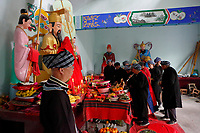 Bouyei priests perform rites at a shrine to celebrate the Lunar March 3rd Festival at Wangmo County in China's southwestern Guizhou Province, April 2019.