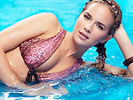 Beauty portrait of a young woman with braided long hair wearing a bikini lying in blue water Image © MaximImages, License at https://www.maximimages.com