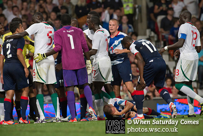 Uruguay 2 United Arab Emirates 1, Great Britain 1 Senegal 1, 26/07/2012. Old Trafford, Olympic Games. Great Britain's Craig Bellamy (blue shirt) lies injured on the ground as an angry confrontation ensues with rival Senegal players at Manchester United's Old Trafford stadium during their team's opening Men's Olympic Football tournament match at the venue. The double header of matches resulted in Uruguay defeating the United Arab Emirates by 2-1 while Great Britain and Senegal drew 1-1. Over 72,000 spectators attended the two Group A matches. Photo by Colin McPherson.