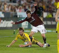Eddie Gaven of the Crew (yellow) is tripped up by the Rapids Terry Cooke (11). The Columbus Crew defeated the Colorado Rapids 2-0, Sunday, July 27, 2008 at Dick's Sporting Goods Park in Denver, Colorado.