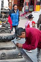 Bodhnath, Nepal.  Nepali Man Praying to a Statue of the Buddha, Prayer Beads in Hand.