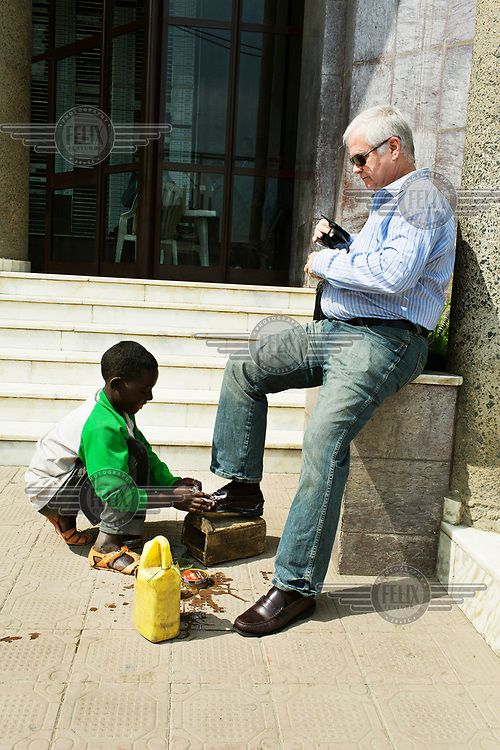 A street child polishes the shoes of a white man outside an office block.