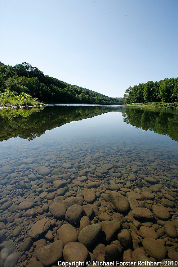 """This view of the Upper Delaware River is at the mouth of Basket Creek, near Long Eddy, NY. The Upper Delaware Scenic and Recreational River, part of the National Park Service's Wild and Scenic Rivers System, stretches 73.4 miles along the New York - Pennsylvania border.<br /> <br /> Hydraulic fracturing or """"fracking"""" is new method of drilling for natural gas: millions of gallons of water, sand and proprietary chemicals are pumped down a well under high pressure. The pressure fractures the shale, opening fissures so that natural gas can flow more freely. In August 2010, fracking is being widely used in the Marcellus Shale formation under Pennsylvania while New York considers a moratorium until the environmental effects can be reviewed. <br /> <br /> The 2005 Energy Policy Act exempted natural gas drilling from the Safe Drinking Water Act (plus some regulations of the Clean Water Act and Clean Air Act), and exempts companies from disclosing the chemicals used during fracking. Scientists have identified volatile organic compounds (VOCs) such as benzene, ethylbenzene, toluene, methane and xylene that have been found in contaminated drinking water near drilling sites. Other environmental concerns include surface water contamination, air pollution, forest fragmentation, plus human health problems. On the other hand, gas companies and property owners stand to earn up to one trillion dollars in profits from drilling in the Marcellus Shale.<br /> <br /> © Michael Forster Rothbart<br /> www.mfrphoto.com <br /> 607-267-4893 o 607-432-5984<br /> 5 Draper St, Oneonta, NY 13820<br /> 86 Three Mile Pond Rd, Vassalboro, ME 04989<br /> info@mfrphoto.com<br /> Photo by: Michael Forster Rothbart<br /> Date: 8/2010    File#:  Canon 5D digital camera frame 68031."""