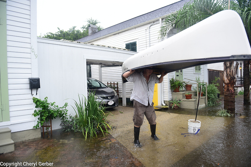 Mark McGrain carries canoe as heavy rains flooded streets in the historic Faubourg Marigny in New Orleans after city pumps were overwhelmed, Sat., Aug. 5, 2017. (Photo by Cheryl Gerber)