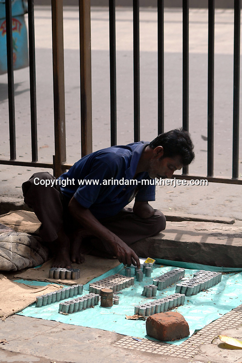 A money changer waits at a foot path for customers with coins. He charges Rs 5 to change a Rs. 100.00 note to a smaller dinominations. Kolkata, West Bengal,  India  7/18/2007.  Arindam Mukherjee/Landov