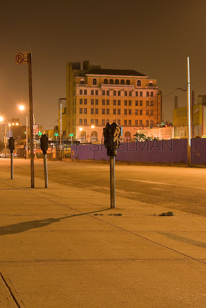 Empty Street, Sidewalk and Parking Meters at Night, Coney Island, Brooklyn, New York City, New York State, USA.  The Shore Building (formerly a movie theater) and Nathan's Famous restaurant visible in the background....Coney Island in transition/before new development has commenced/summer of 2007