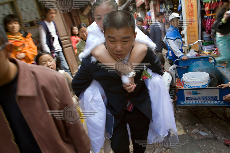 Cheered on by onlookers, a groom carries his bride from the main city square to their home, as is customary in Nakhi (Naxi) tradition. They are in the market in the old city of Lijiang, a centre of Nakhi culture which is a UNESCO World Heritage Site.