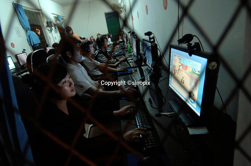 Teenagers playing online game at an internet cafe in Jinghong, China. Online gaming is a massive industry in China with over 137 million users generating a massive profits for the leading online gaming comapanies such as NCsoft, Global Gaming League, etc..22 Mar 2008