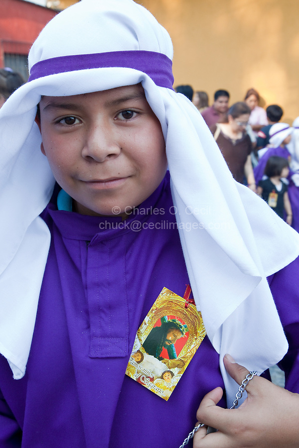 Antigua, Guatemala.  A Young Boy Cucurucho in a Procession during Holy Week, La Semana Santa.  The white specks on his face are ashes from the incense pot he is carrying.