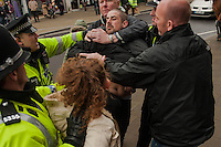 Saturday 05 April 2014<br /> Pictured: A man is held back by police<br /> Re: White Pride and Anti Fascist groups protest in Swansea City Cebtre