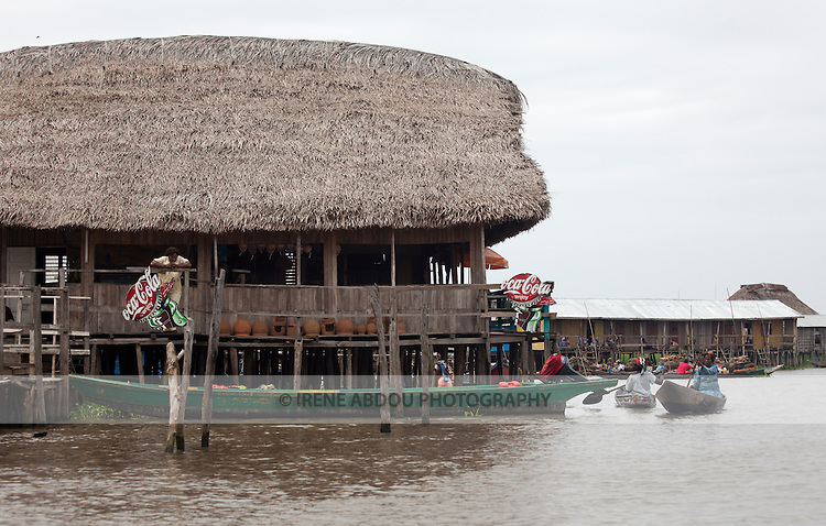 """Ganvie, Benin, with some 3,000 stilted buildings and a population of 20,000-30,000 people, may be the largest """"lake vllage"""" in Africa.  In Ganvie, the population lives exclusively from fishing, building houses on stilts in and next to Lake Nokoue.  Because the Dan-Homey religion prohibited attacks on communities living in the water, the village of Ganvie dates back to the 16th or 17th century, when it was built to protect people from slavery.  Yet, even Ganvie hasn't escaped Coca Cola!!!"""