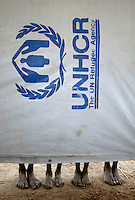 Displaced persons who are sheltered at a refugee camp stand behind a tarpaulin bearing the logo of the United Nations (UN) High Commission for Refugees (UNHCR).
