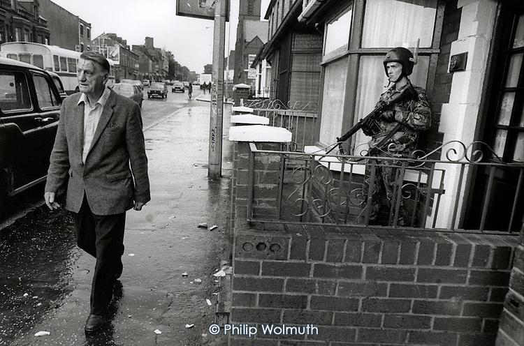 A man walks past a British soldier on foot patrol in the Falls Road, Belfast.
