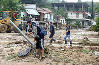 Local people walk in muddy streets full of debris in Agia Triada