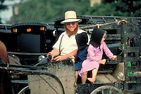 An Amish father and two five and six year old Amish girls wearing large bonnets enjoy an open farm buggy ride to market. Amish father and children. Kidron Ohio United States market.