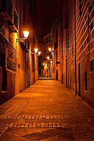 Narrow alley illuminated by street lamps at night, Madrid, Spain