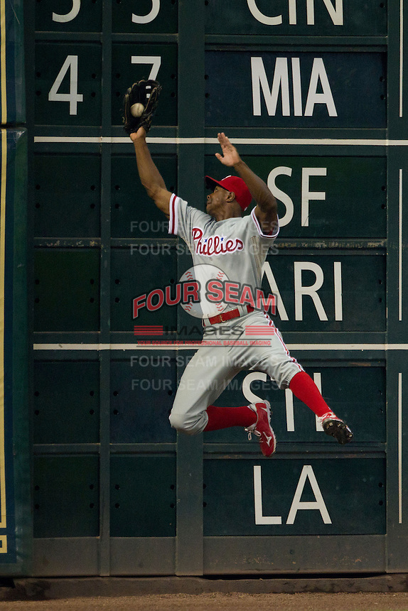 Philadelphia Phillies outfielder Juan Pierre #10 makes a leaping catch during the Major League baseball game against the Houston Astros on September 16th, 2012 at Minute Maid Park in Houston, Texas. The Astros defeated the Phillies 7-6. (Andrew Woolley/Four Seam Images).