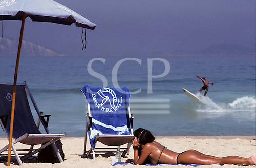 Rio de Janeiro, Brazil. Pretty girl on the beach with a surfer behind, a sunshade and a chair with a Caesar Park Hotel towel.