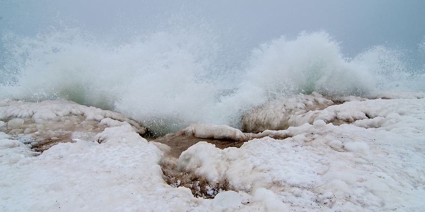 A large Lake Superior wave explodes when it hits the icy shoreline. Marquette, MI
