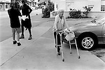 SOUTH BEACH MIAMI, FLORIDA - USA 1999: OLD WOMAN WITH ZIMMER FRAME WALKING PAST AN AFRO AMERICA MAN WHO IS DRESSED AS A SUPER HERO. HE IS WEARING HIS UNDER SHORTS OVER HIS BLACK COSTUME WHILE BEING FILMED.