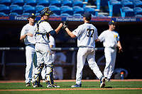 Michigan Wolverines catcher Harrison Salter (11) fist bumps starting pitcher Karl Kauffmann (37) in between innings during a game against Army West Point on February 18, 2018 at Tradition Field in St. Lucie, Florida.  Michigan defeated Army 7-3.  (Mike Janes/Four Seam Images)