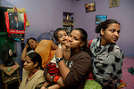 INDIA (West Bengal - Calcutta)July 2007,Shakila Babe(right) and Sanno Babe (left) with their family at their  small two roomed apartment in Iqbalpur.  10 family members share this apartment.   Shakila and Shanno are twins from a poor muslim family of Iqbalpur, Kolkata. . Inspite of their late father's unwillingness to send his daughters to take up  boxing her mother Banno Begum inspired them to take up boxing at the age of 3. Their father was more concerned about the social stigma they have in their community regarding women coming into sports or doing anything which may show disrespect to the religious emotions of his community. Shakila now has been recognised as one of the best young woman boxers of the country after she won the  international championship at Turkey in the junior category. Shanno is also been called for the National camp this year. Presently Shakila and shanno has become the role model in the Iqbalpur area  and parents from muslim community of Iqbalpur have started showing interst in boxing. Iqbalpur is a poor muslim dominated area mostly covered with shanty town with all odds which comes along with poverty and lack of education. - Arindam Mukherjee