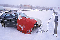 Cars plugged into headbolt heaters to keep engines warm enough to start at the University of Alaska during chilly winter conditions.
