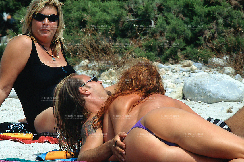 """Spain. Ibiza in the Balearic islands. Ibiza. Mediterranean sea. Beach """" Calo Jondal"""". Tourists take a rest and sunbathe. A  couple holds each other in the arms. © 1999 Didier Ruef"""
