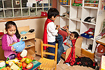 Education Preschool 3-4 year olds girl playing quietly in pretend play/family area as two boys enact punching superhero drama