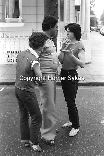 Earls Court, London. 1977<br /> Two rent boys use sign and body language to ask a male Arab healthcare tourist if he would like to join them.