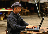 Old Chinese man on laptop computer in Shanghai China.