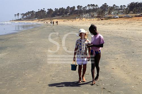 Banjul, Gambia. Two young girls, one black, one white, walking along the beach.