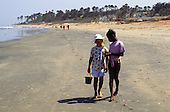 Banjul, Gambia. Two young girls, one black, one white, walking along the beach.