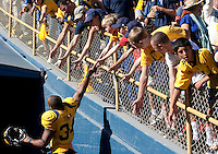 Shane Vereen jumps to reach the hands of fans on his way off the field. The California Golden Bears defeated the UCLA Bruins 35-7 at Memorial Stadium in Berkeley, California on October 9th, 2010.