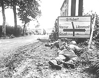 Men of the 8th Infantry Regiment attempt to move forward and are pinned down by German small arms from within the Belgian town of Libin.  Men seek cover behind hedges and signs to return the fire.  September 7, 1944.  Gedicks.  (Army)<br /> NARA FILE #:  111-SC-193835<br /> WAR & CONFLICT BOOK #:  1061