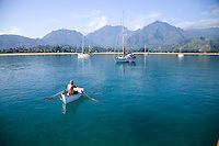 Man rowing dinghy off of his sailboat in Hanalei Bay, Kauai