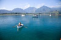 Man rowing dinghy off of his sailboat in Hanalei Bay, Kauai
