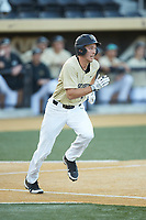 D.J. Poteet (4) of the Wake Forest Demon Deacons watches the flight of his grand slam as he hustles down the first base line during the game against the Liberty Flames at David F. Couch Ballpark on April 25, 2018 in  Winston-Salem, North Carolina.  The Demon Deacons defeated the Flames 8-7.  (Brian Westerholt/Four Seam Images)