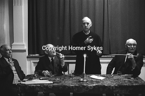 Aldermaston Candle Auction, Berkshire, England 1974. Fr L-R , C. W. 'Bill' Cox, churchwarden, Dr Allibone, who is Lord of the Manor. The Rev'd Ross Stone and  Major General Benson,churchwarden. The auction takes place every three years. (Names thanks to Dave Shirt)<br /> <br /> In 1974, the traditional hot run punch was not served, just hot punch. A tallow candle made by Dr Allibone in 1962 was used, an inch is burnt each year. A pin or horse shoe nail is inserted just below the wick, and bidding continues until it falls out. The last bid before this happens secures the lease on Church Acre for three years. The sum being bid represents annual rent. A record bid of £50-50 was recorded in 1974. The Church Acre is in fact 2 acre, 1 rod, 33 poles and is situated just beyond Fisherman Cottage. The renting goes back to at least 1801 when the successful bid was £7-00. There after is has been rented for varying periods, 1 yr, 6 yrs and 7 yrs. Since 1866 it has always been rented for a 3 yr period. the present Church Acre was an award under the Inclosure's Act of 1811 which became effective in 1815.What ground was auctioned before that is unknown, but probably part of the Common.<br /> <br /> (from my 1974 notes, the candle is good at least until 2000.)