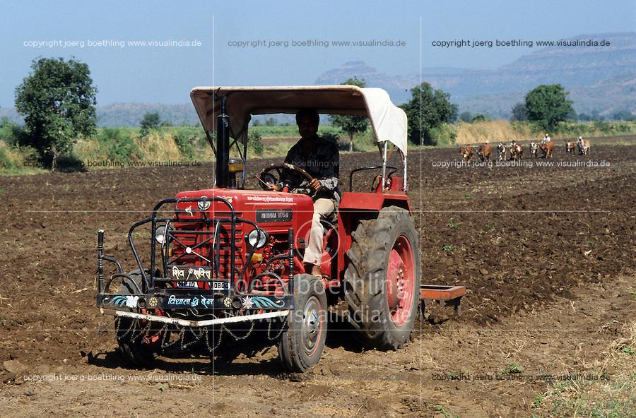 INDIEN Mahindra Traktor und Ochsengespanne beim Pfluegen eines Feldes fuer den Baumwollanbau- INDIA Madhya Pradesh , contrast Mahindra tractor and ox ploughing of cotton field