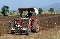 INDIEN Mahindra Traktor und Ochsengespanne beim Pfluegen eines Feldes fuer den Baumwollanbau- INDIA Madhya Pradesh , contrast Mahindra tractor and ox ploughing of cotton field