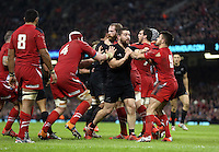 Pictured: A fight breaks out between Dane Coles (in black) of New Zealand and Wales players Saturday 22 November 2014<br /> Re: Dove Men Series 2014 rugby, Wales v New Zealand at the Millennium Stadium, Cardiff, south Wales, UK.