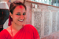 Kathmandu, Nepal.  Hindu Woman Visiting Neighborhood Temple to the God Hanuman.  A Tika Mark of Sindur Powder and Rice is on her Forehead.