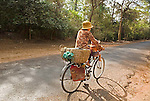 Cambodian woman laughs riding bicycle with female toddler in front basket sling on sunny empty road