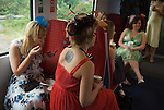 A group of young nurses on the train to Royal Ascot horse race. Ascot, Berkshire. England. 2006.
