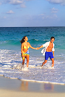 Playful couple walking in the surf